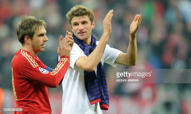 Munich's Thomas Müller and Philipp Lahm applaud the fans after the UEFA Champions League soccer round of sixteen between FC Bayern Munich and Arsenal...