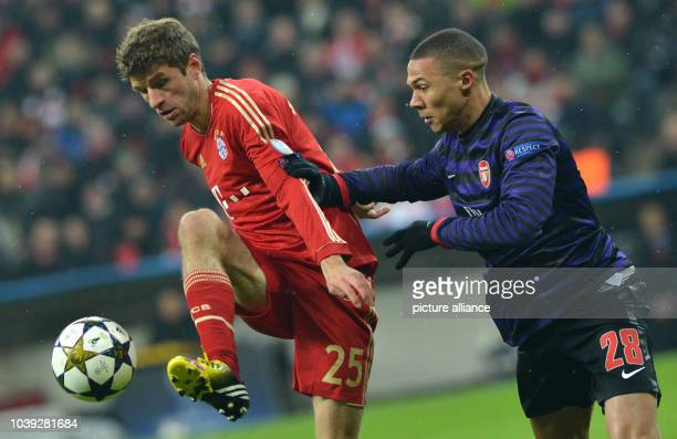 Munich's Thomas Mueller and Arsenal's Kieran Gibbs vie for the ball during the Champions League round of 16 second leg soccer match between FC Bayern...