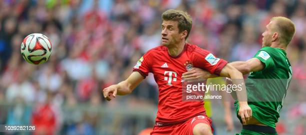 Munich's Thomas Mueller and Augsburg's Ragnar Klavan compete for the ball during the German Bundesliga soccer match between Bayern Munich and FC...