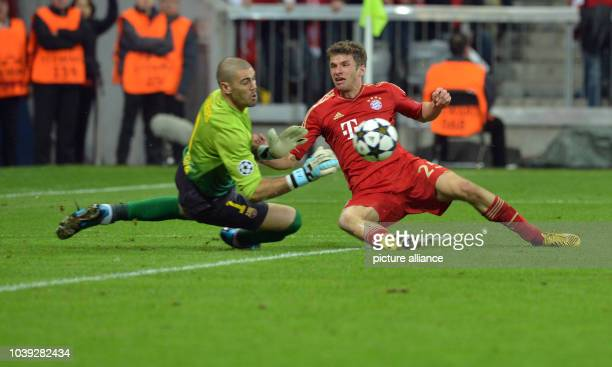 Munich's Thomas Mueller vies for the ball with Barcelona's goalkeeper Victor Valdes during the UEFA Champions League semi final first leg soccer...