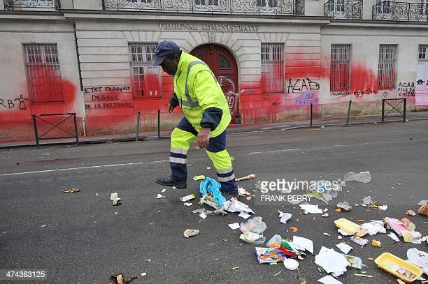 A municipal agent cleans the street in front of the tagged facade of the Tribunal Administratif in Nantes western France on February 23 2014 a day...