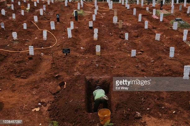 A municipal cemetery worker digs a grave in a special cemetery for suspected Covid19 Coronavirus victim on September 11 2020 in Jakarta Indonesia...