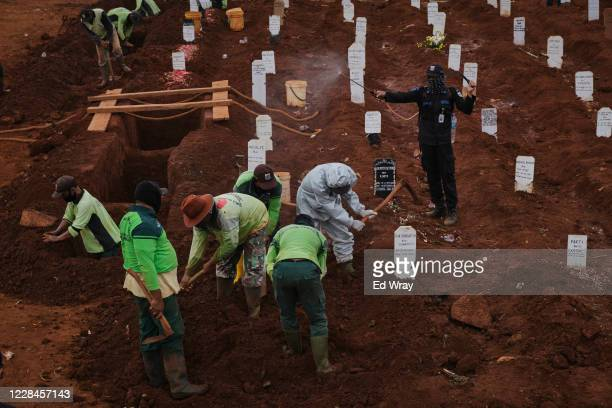 Municipal cemetery workers are sprayed with disinfectant as they bury a suspected victim of the Covid-19 Coronavirus in a special cemetery for...