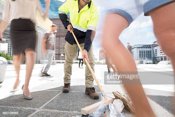 municipal cleaner sweeping rubbish between a crowd of people in a city - street sweeper stock pictures, royalty-free photos & images