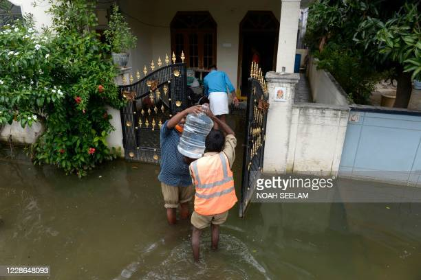 Municipal Corporation employees supply drinking water and food to stranded residents following heavy monsoon rainfalls in Meerpet, on the outskirts...