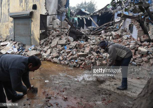 Municipal Corporation of Delhi employees clear the debris of a collapsed building after an explosion in New Delhi on January 4 2019 Six people...