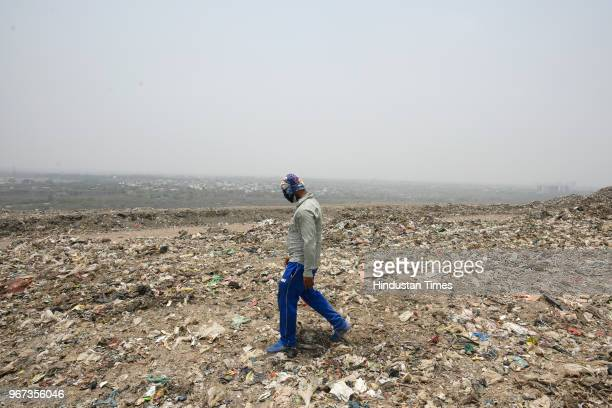 Municipal corporation official walks on a mountain formed by garbage at a landfill site ahead of the World Environment Day, at Okhla on June 4, 2018...