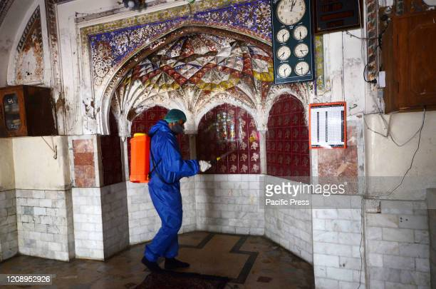 Municipal corporation team members spray disinfectant to sanitize the surroundings of the Dilawar Khan Mosque and street following an outbreak of the...