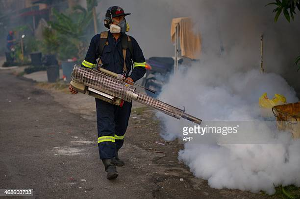 A municipal council worker dispenses insecticide using a fogging machine during a dengue prevention spraying in Ampang in the suburbs of Kuala Lumpur...