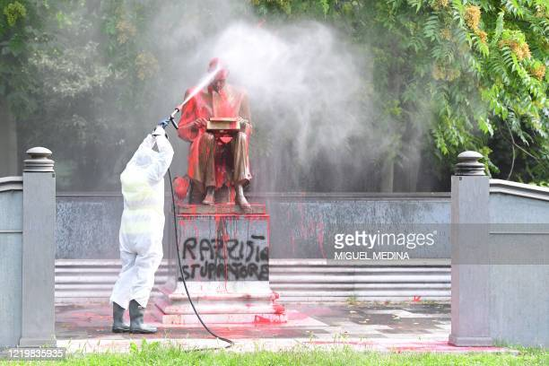 A municipal employee cleans a statue of a famous Italian journalist Indro Montanelli on June 14 2020 in a Milan public square a day after it was...