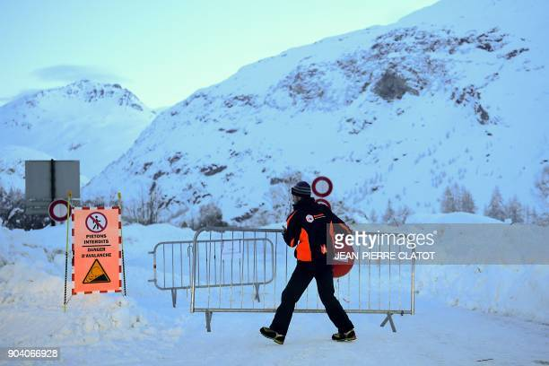 A municipal employee moves barriers as he temporarily opens a road for cars to drive in a convoy from Bessans to BonnevalsurArc in the French Alps on...