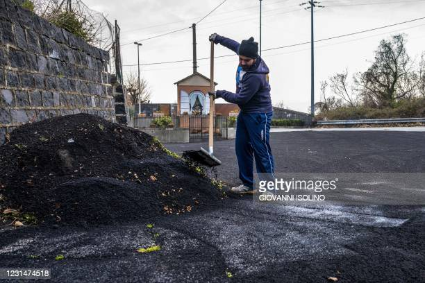 Municipal employee sweep ashes from the Mount Etna volcano from a street of Milo, north of Catania, Sicily, on March 02, 2021. - Mount Etna, one of...