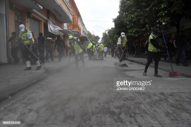 Municipal employees sweep up ash after the eruption of the Fuego Volcano in Guatemala City on June 3 2018
