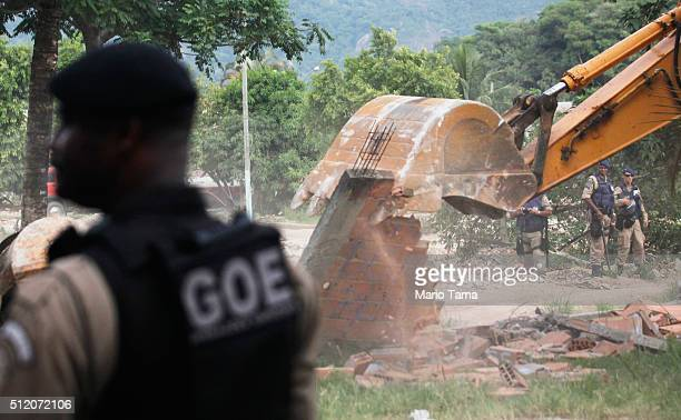 Municipal Guard police keep watch during the demolition of the residents association building in the mostly demolished Vila Autodromo favela...