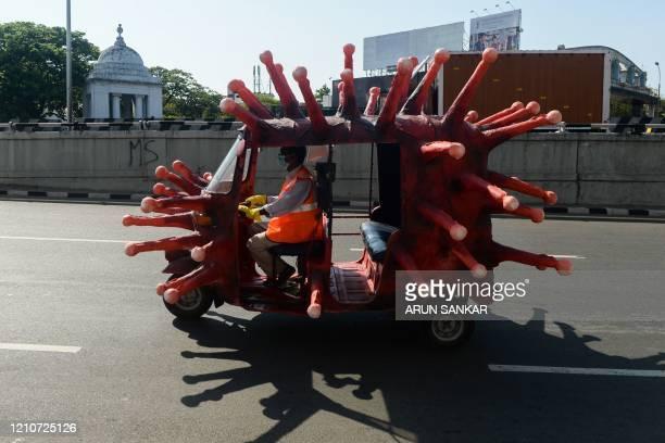 Municipal health worker drives an auto-rickshaw decorated as a coronavirus model along a road to raise awareness about the COVID-19 coronavirus...