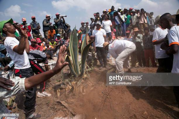 Municipal officers clear the ground which blocks the entrance of a family vault during a funerary tradition called the Famadihana in the village of...