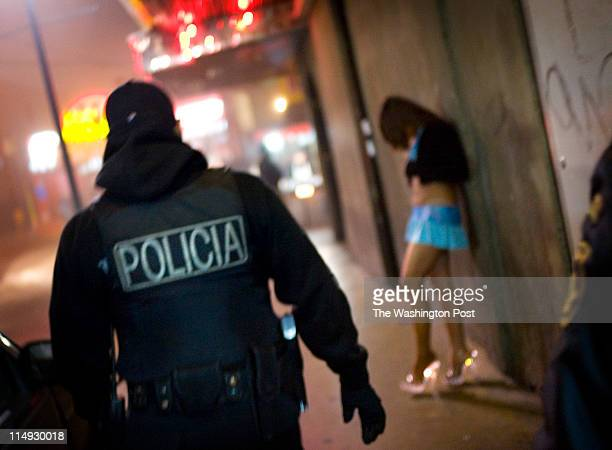A municipal police officer walks past a prostitute in the North Zone of downtown Tijuana In the city the estimated number of drug addicts and small...