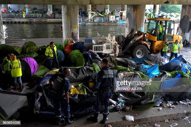 Municipal police officers of the city of Paris and workers clean up the Millenaire migrants makeshift camp along the Canal de SaintDenis near Porte...