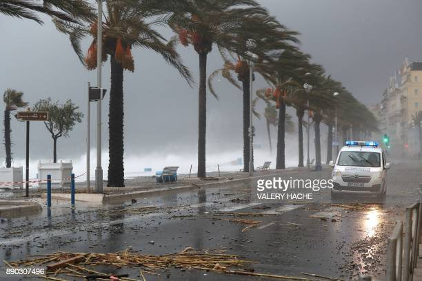 TOPSHOT A municipal police van drives on the landmark Promenade des Anglais avenue as massive waves break against the shore in the French riviera...