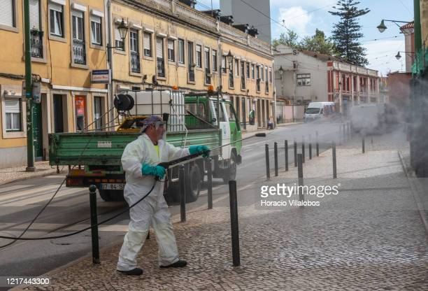 Municipal sanitary workers wear protective gear while disinfecting Rua 1º de Maio in Alcantara neighborhood due to the COVID19 Coronavirus emergency...
