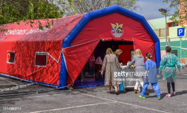 Municipal staffers push a cart with elements for the triage station set up using a firefighters tent by Oeiras municipality to check patients for...