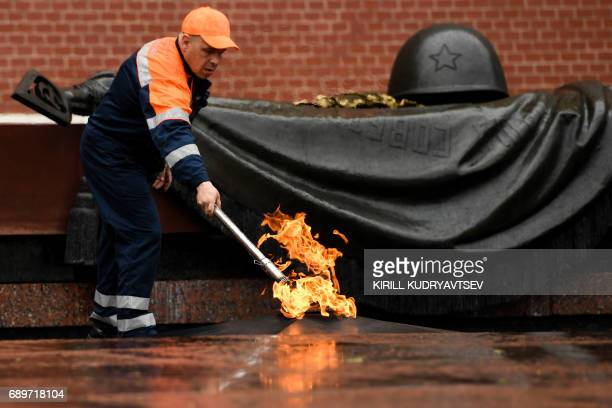 A municipal worker checks the eternal flame in Moscow's Alexander Garden following a storm on May 29 2017 / AFP PHOTO / Kirill KUDRYAVTSEV