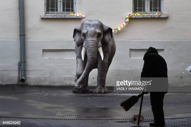 A municipal worker cleans a sidewalk next to an elephant sculpture in front of the State Museum of Oriental Art in central Moscow on March 7 2017 /...