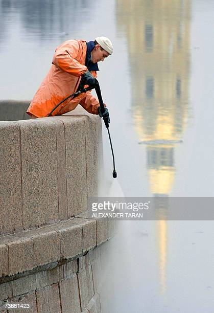 A municipal worker cleans an embankment as the cathedral of Peter and Paul fortress is reflected on the Neva river in StPetersburg 23 March 2007 AFP...