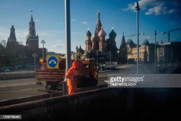 Municipal worker cleans and disinfects a bridge near the Kremlin in downtown Moscow on April 12 during a strict lockdown in Russia to stop the spread...