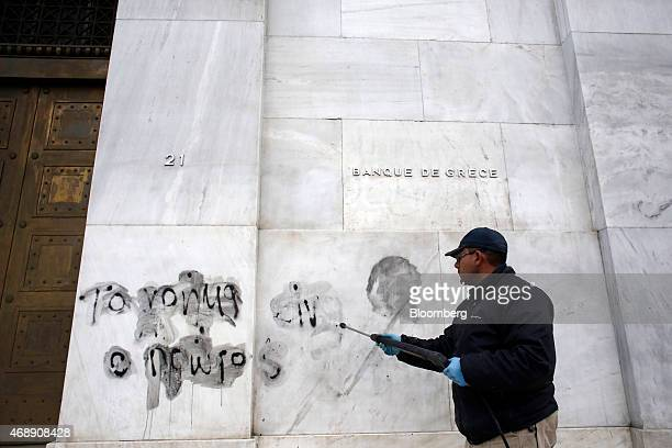 A municipal worker cleans graffiti reading Money is the first terrorist from a wall outside the headquarters of the Bank of Greece SA in Athens...