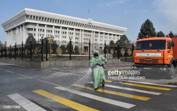 Municipal worker disinfects a street in front of the Parliament as a measure against the COVID-19 coronavirus pandemic in Bishkek on March 26, 2020.