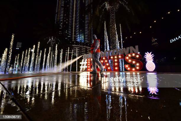 A municipal worker disinfects the streets as a preventive measure against the spread of COVID19 in downtown Dubai on March 27 2020 The United Arab...
