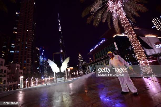 A municipal worker disinfects the streets as a preventive measure against the spread of COVID19 as the Burj Khalifa is seen in the background in...