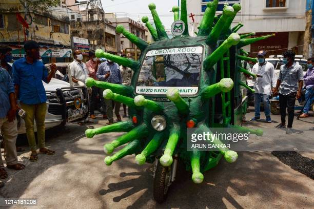 Municipal worker drives a coronavirus-themed auto-rickshaw in a street of a residential area after the government eased a nationwide lockdown imposed...