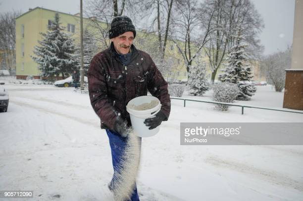 Municipal worker is seen sprinkling salt in Bydgozcz, Poland on January 16, 2018. More snow is expected for the coming days across the country and...