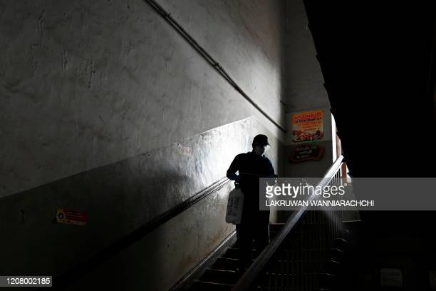 A municipal worker sprays disinfectant during a nationwide curfew imposed by the Sri Lankan government as a preventive measure against the COVID19...