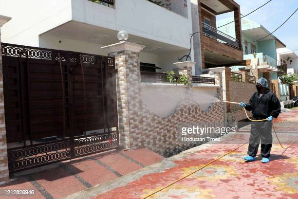 A municipal worker sprays disinfectant in a residential area during lockdown on May 12 2020 in Jammu India