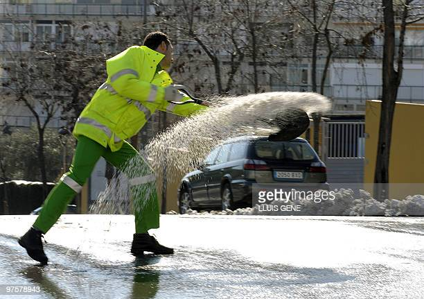 Municipal worker spreads salt on a street of Barcelona on March 9, 2010 after a heavy snowfall. Barcelona saw its heaviest snowfall since 1962,...
