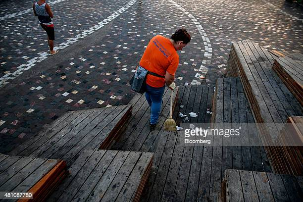 A municipal worker sweeps rubbish from a wooden platform on Monastiraki square in Athens Greece on Friday July 17 2015 Germany's Parliament is set to...