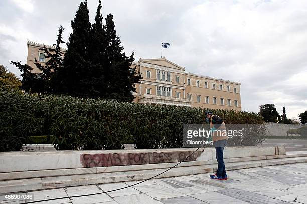 A municipal worker uses a high pressure hose to clean anarchist graffiti from a wall outside the Greek parliament building in Athens Greece on...