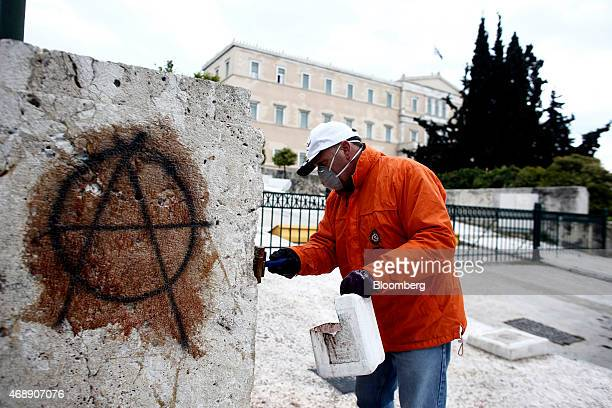A municipal worker uses chemicals to clean anarchist graffiti from a wall outside the Greek parliament building in Athens Greece on Wednesday April 8...