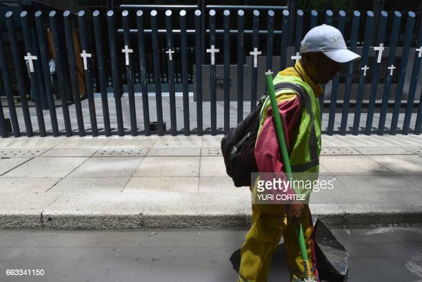 A municipal worker walks past a metal fence where members of the Early Warning for Journalists National Collective placed crosses representing...