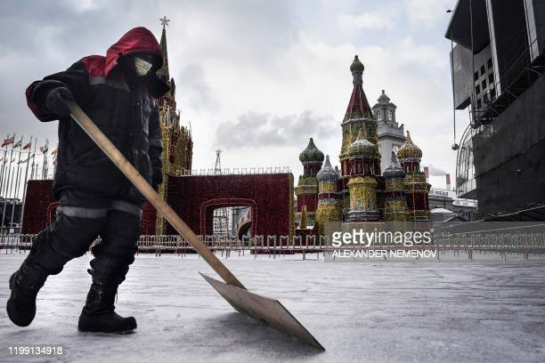 Municipal worker wearing medical face mask cleans the snow in front of a model of Saint Basil cathedral, in Moscow, on February 7, 2020. - Russian...