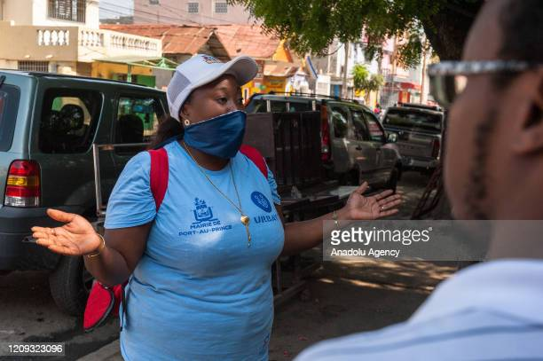 Municipal worker, with her face covered, warns citizens against the coronavirus pandemic in Port-au-Prince, Haiti on April 06, 2020.