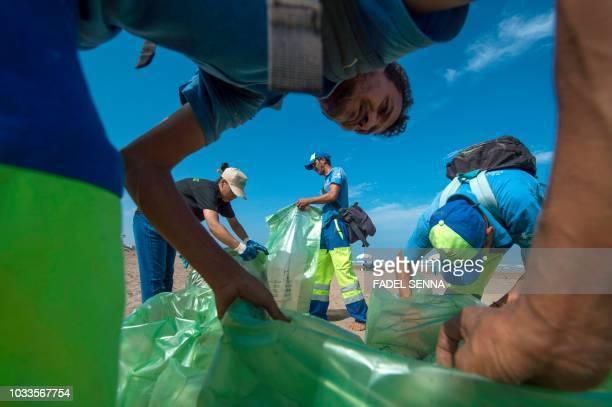 Municipal workers and a Greenpeace activist take part in cleaning the beach of Ain Diab in the Moroccan city of Casablanca on September 15 during...