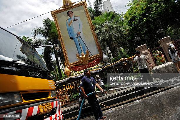 Municipal workers and volunteers clean up a road past a portrait of Thai King Bhumibol Adulyadej four days after an army assault on an antigovernment...