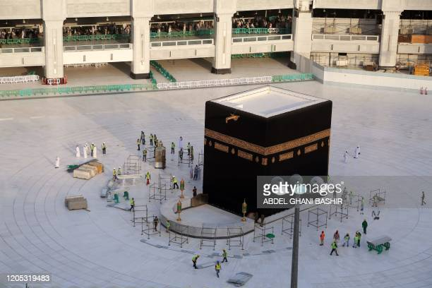 Municipal workers are pictured in empty whitetiled area surrounding the Kaaba inside Mecca's Grand Mosque on March 5 2020 Saudi Arabia today emptied...
