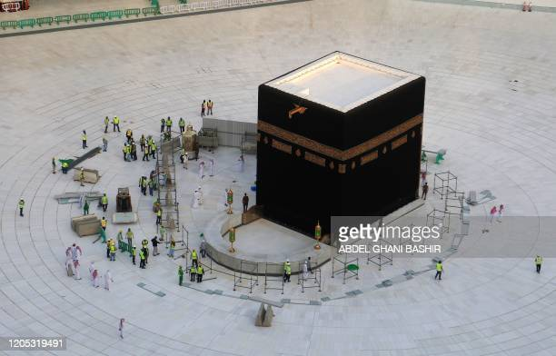TOPSHOT Municipal workers are pictured in empty whitetiled area surrounding the Kaaba inside Mecca's Grand Mosque on March 5 2020 Saudi Arabia today...