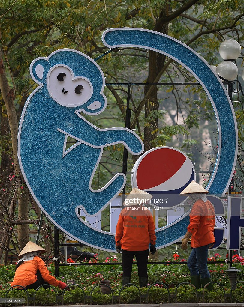 Municipal workers arrange flowers next to a decoration bearing the image of a monkey in downtown Hanoi on February 3, 2016 as Vietnamese prepare to celebrate the Lunar New Year, or Tet. Vietnamese will mark the Lunar New Year, this year the Year of the Monkey in the Chinese Zodiac, along with many countries in east Asia, on February 8. AFP PHOTO / HOANG DINH Nam / AFP / HOANG