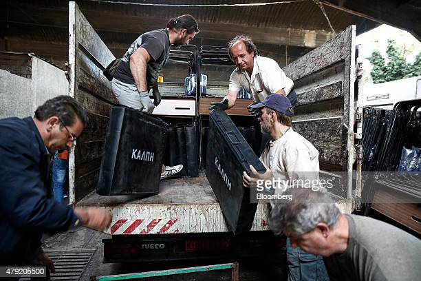 Municipal workers carry ballot boxes as they prepare to transfer them to schools for Sunday's referendum inside a warehouse in Athens Greece on...